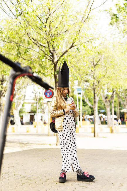 Girl wearing golden sequin jacket, polka dot jumpsuit and black crown drinking soft drink on the street — Stock Photo