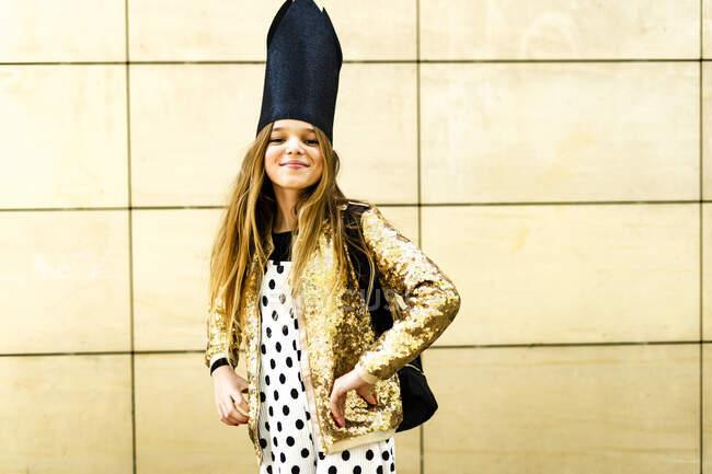 Portrait of smiling girl wearing golden sequin jacket, polka dot jumpsuit and black crown — Stock Photo