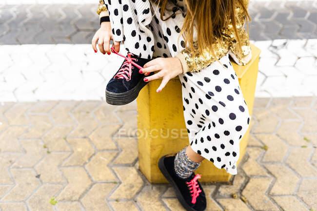Girl sitting on bollard tying shoe, partial view — Foto stock