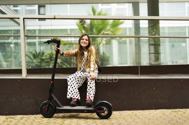 Portrait of smiling girl with E-Scooter wearing golden sequin jacket and polka dot jumpsuit — Stock Photo