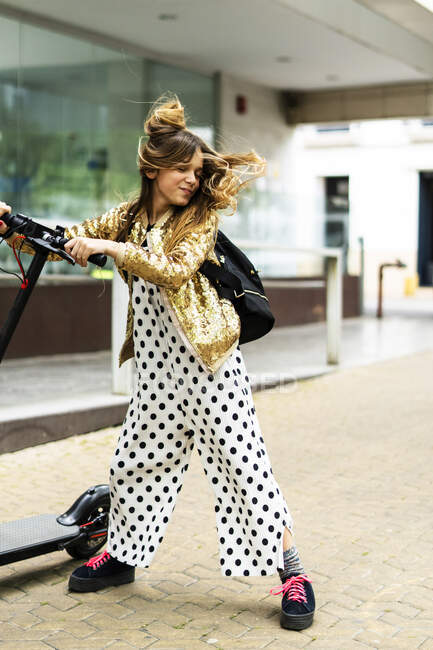 Portrait of smiling girl with E-Scooter wearing golden sequin jacket and polka dot jumpsuit tossing her hair — Stock Photo