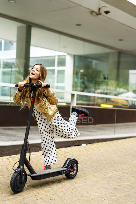 Portrait of laughing girl with E-Scooter wearing golden sequin jacket and polka dot jumpsuit — Stock Photo