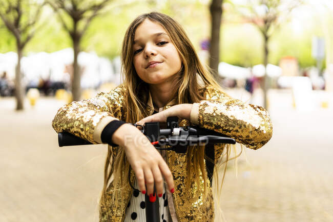 Portrait of girl wearing golden sequin jacket leaning on handlebar of E-Scooter — Stock Photo