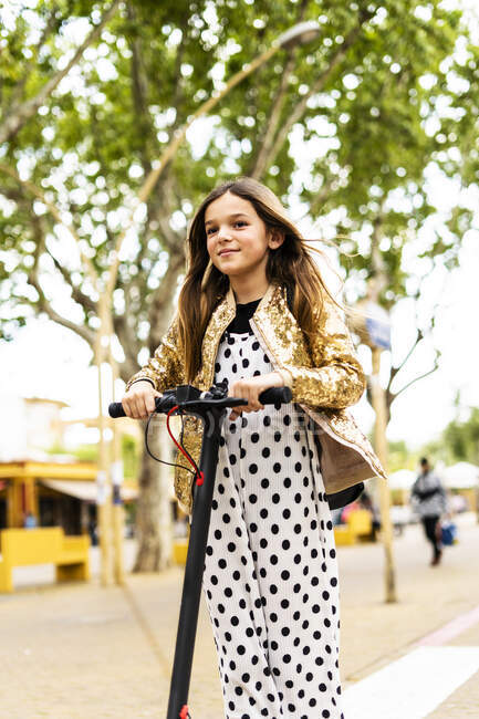 Portrait of smiling girl wearing polka dot jumpsuit on E-Scooter — Stock Photo