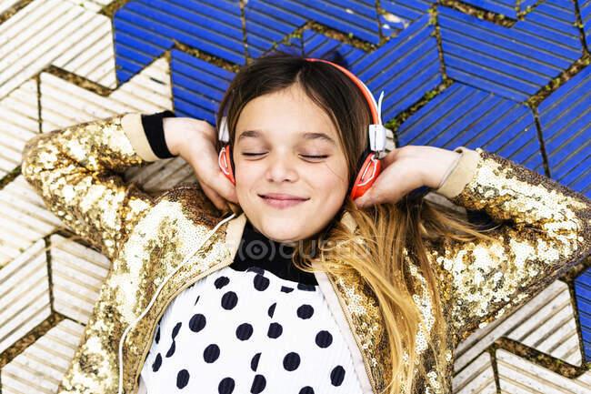 Portrait of happy girl wearing golden sequin jacket listening music with headphones — Stock Photo