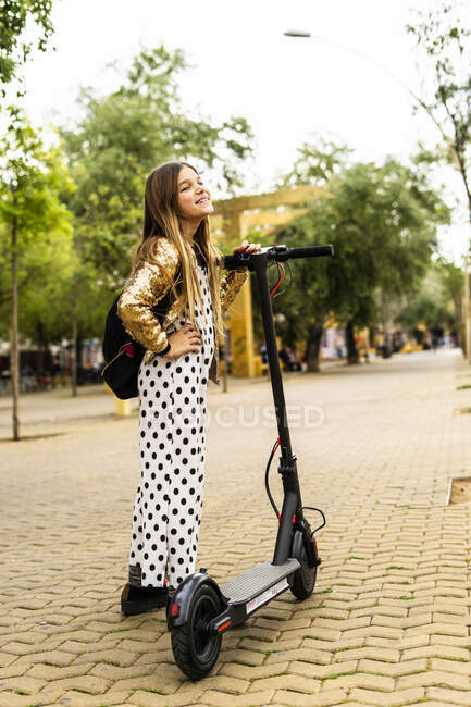 Happy girl with E-Scooter wearing golden sequin jacket and polka dot jumpsuit — Stock Photo