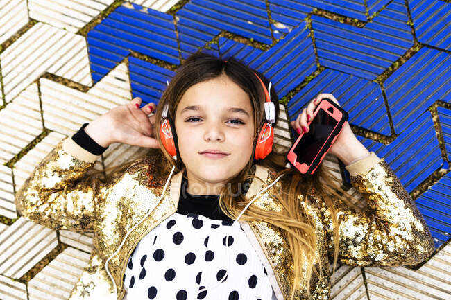 Portrait of girl wearing golden sequin jacket listening music with headphones and smartphone — Stock Photo