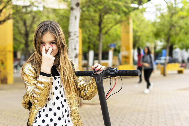 Portrait of smiling girl with scooter wearing golden sequin jacket — Stock Photo