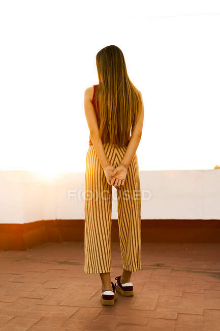 Rear view of teenage girl standing on roof terrace at sunset — Stock Photo