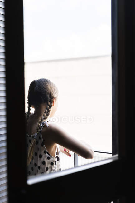 Rear view of girl wearing dotted dress looking from balcony — Stock Photo