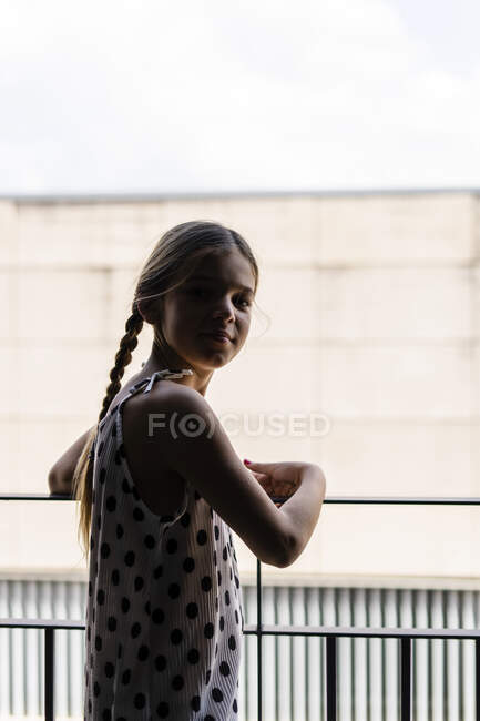 Girl wearing dotted dress standing on balcony — Stock Photo