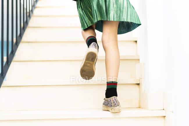 Girl wearing green skirt running upstairs — Foto stock