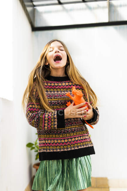 Happy girl playing with dinosaur toy at home - foto de stock
