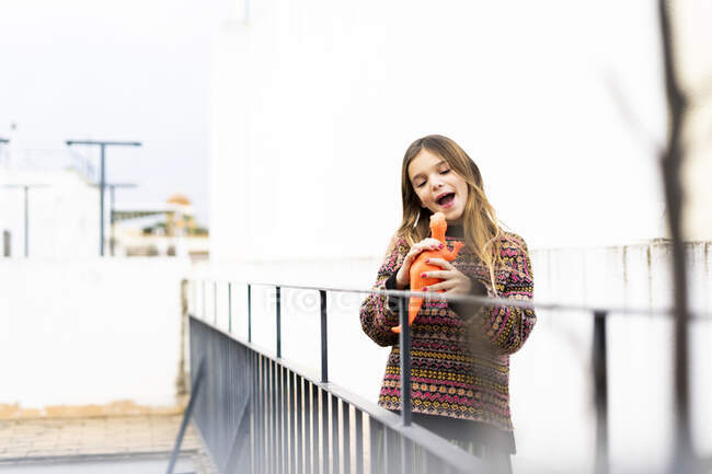 Happy girl playing with dinosaur toy on roof terrace - foto de stock