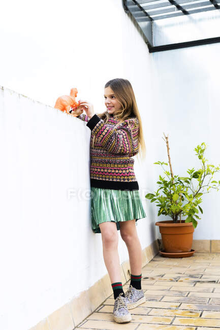 Girl playing with dinosaur toy at home - foto de stock