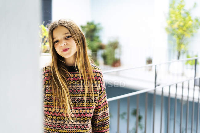 Portrait of smiling girl wearing patterned pullover — Stock Photo