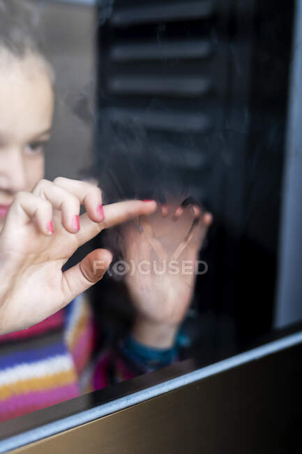 Primer plano del corazón de dibujo de niña en el cristal de la ventana empañada - foto de stock