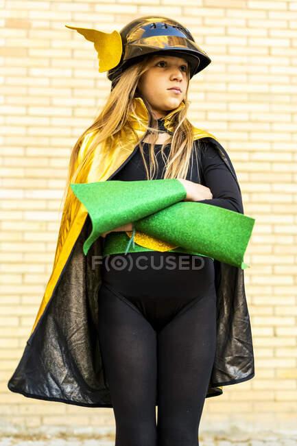 Дівчинка в костюмі супергероїні, що поставлена на цегляній стіні. — стокове фото