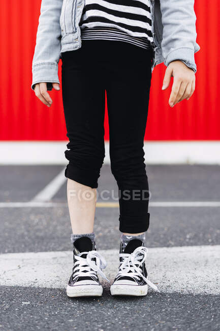Girl with one trouser leg rolled up, partial view — Stock Photo
