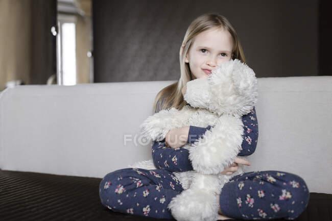 Retrato de niña sonriente usando pijama con diseño floral sosteniendo oso de peluche blanco - foto de stock