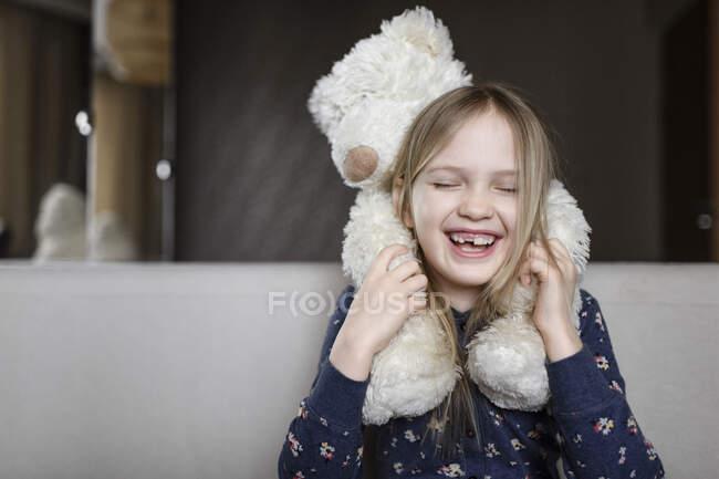 Retrato de niña riendo con hueco dental sosteniendo oso de peluche blanco - foto de stock