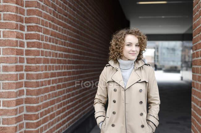 Retrato de mulher sorridente com cabelo encaracolado vestindo casaco bege e pulôver de gola alta — Fotografia de Stock