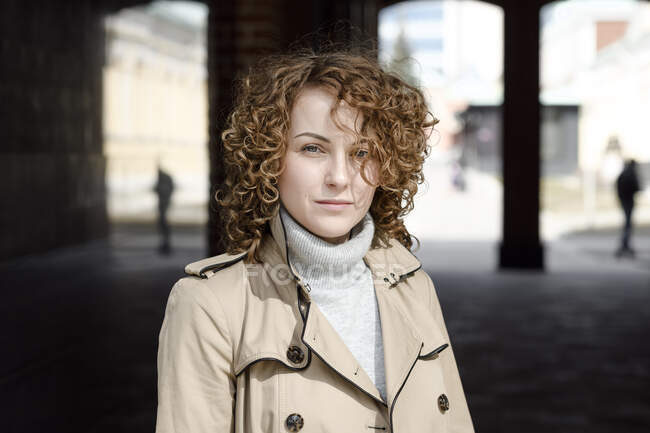 Retrato de mulher com cabelo encaracolado vestindo casaco bege e pulôver de gola alta — Fotografia de Stock