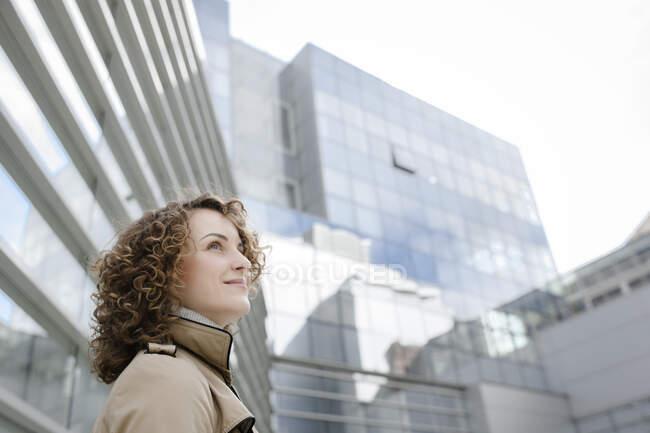 Mulher sorridente com cabelo encaracolado na frente da arquitetura moderna olhando para cima — Fotografia de Stock