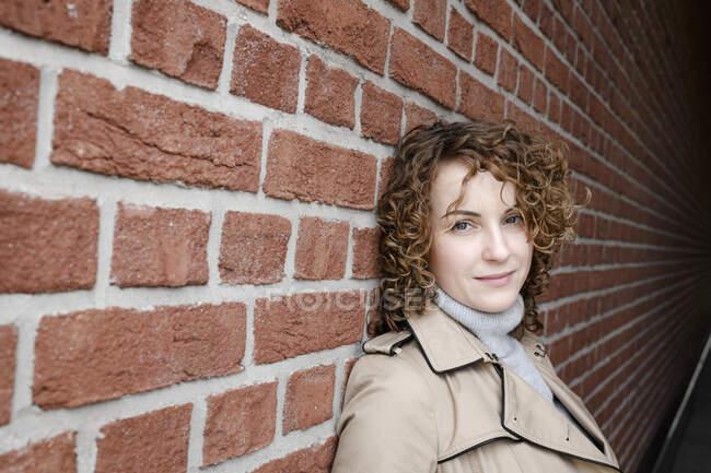 Retrato de mulher com cabelo encaracolado vestindo casaco bege encostado à parede de tijolo — Fotografia de Stock