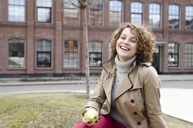Retrato de mulher feliz com cabelo encaracolado sentado em um prado comendo uma maçã — Fotografia de Stock