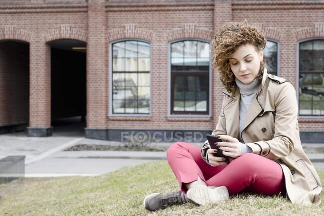 Retrato de mulher com cabelo encaracolado sentado em um prado olhando para o telefone celular — Fotografia de Stock