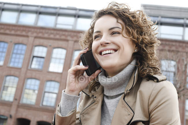 Retrato de mulher feliz com cabelo encaracolado no telefone — Fotografia de Stock