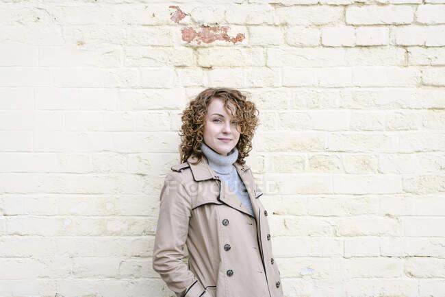 Retrato de mulher sorridente com cabelo encaracolado vestindo casaco bege — Fotografia de Stock
