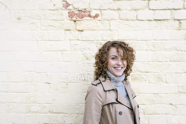 Retrato de mulher feliz com cabelo encaracolado na frente da parede de tijolo — Fotografia de Stock