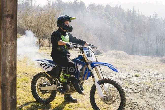Conductor de motocross en moto con humo saliendo del tubo de escape - foto de stock