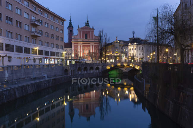 Slovenia, Ljubljana, view to city centre with Franciscan Church and lighted Triple Bridge — Stock Photo