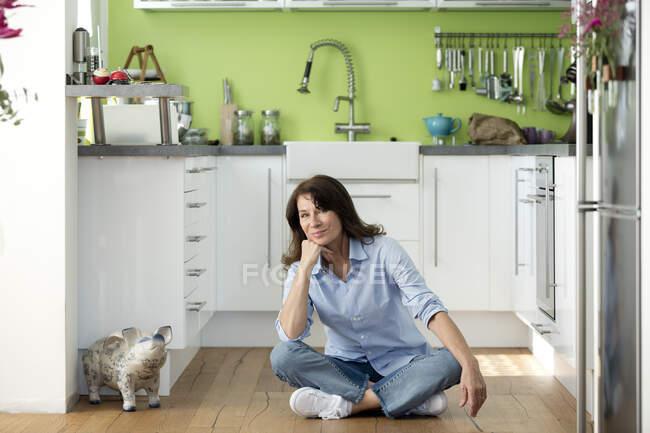 Retrato de mujer madura sentada en el suelo en la cocina en casa - foto de stock