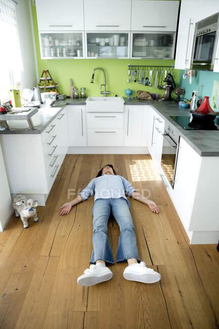 Mujer madura tumbada en el suelo en la cocina en casa - foto de stock