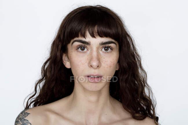 Retrato de mujer joven tatuada con pecas - foto de stock