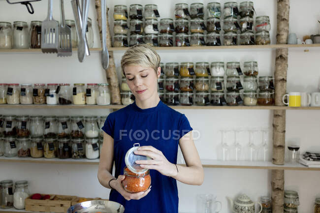 Жінка відкриває банку перед шельфовою спецією на кухні. — стокове фото