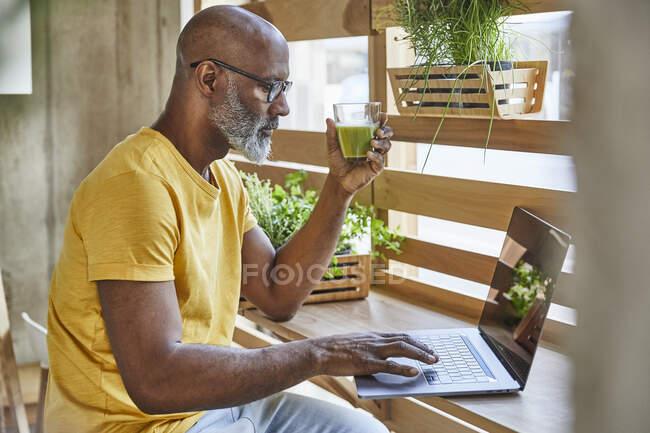 Зрілий бізнесмен з коктейлем за допомогою ноутбука біля вікна в офісі. — стокове фото