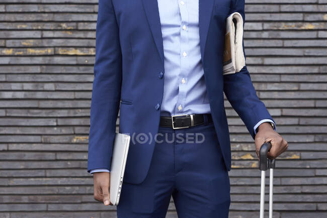 Businessman with newspaper, laptop and trolley bag wearing blue suit, partial view — Stock Photo