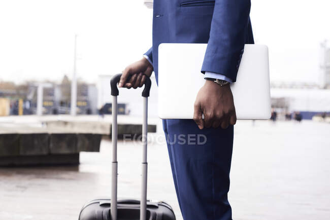 Waiting businessman with laptop and trolley bag wearing blue suit, partial view — Stock Photo