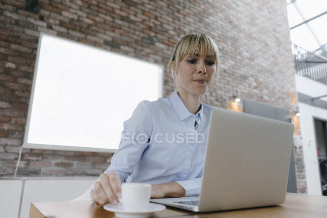 Businesswoman working on laptop, drinking coffee, licking lips — Stock Photo