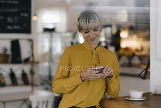 Donna d'affari bionda che usa lo smartphone in una caffetteria, legge messaggi di testo — Foto stock