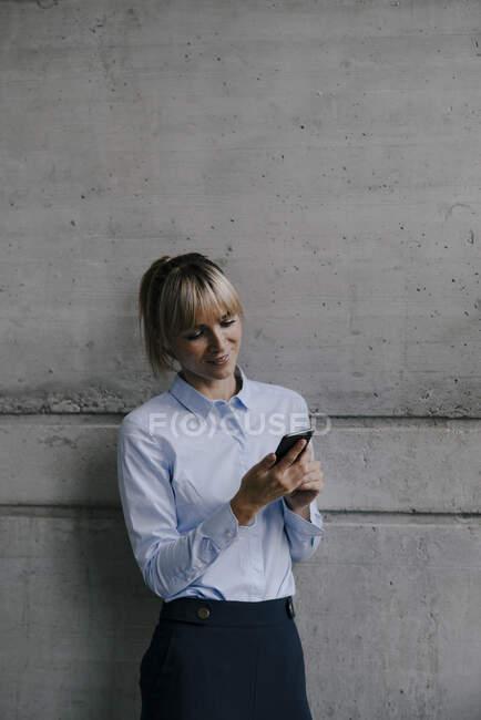 Lunga donna d'affari utilizzando smartphone, lettura di messaggi — Foto stock