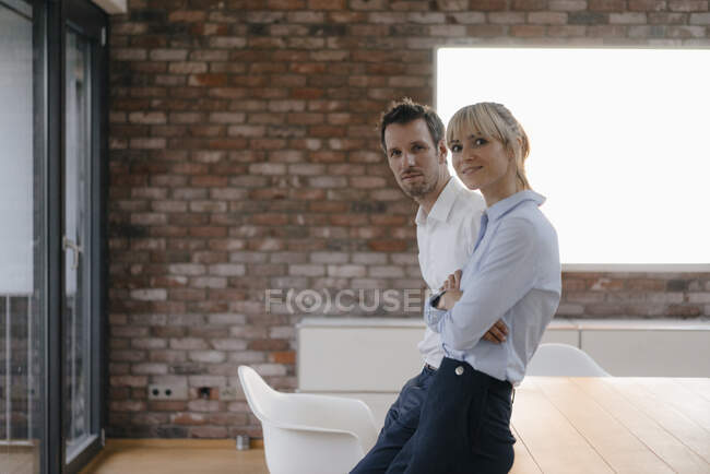 Successful businessman and woman standing in their boardroom, smiling — Stock Photo
