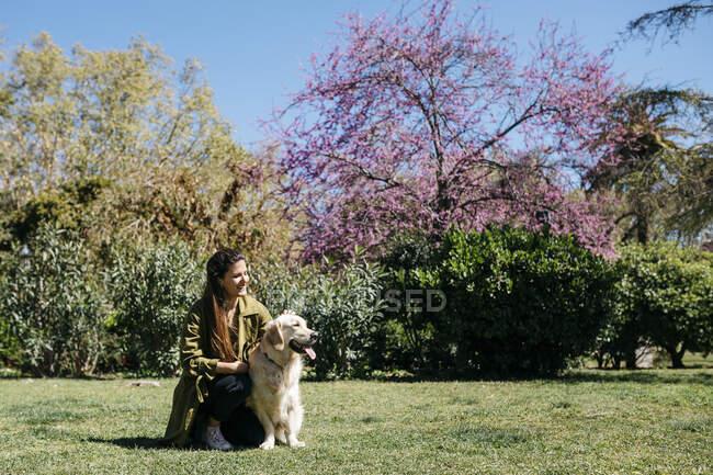 Happy woman stroking her Labrador Retriever on meadow in city park — Stock Photo