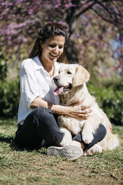 Happy woman sitting on meadow in city park with her Labrador Retriever — Stock Photo