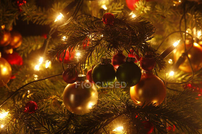 Christmas tree with Christmas baubles and light chains, partial view — Stock Photo